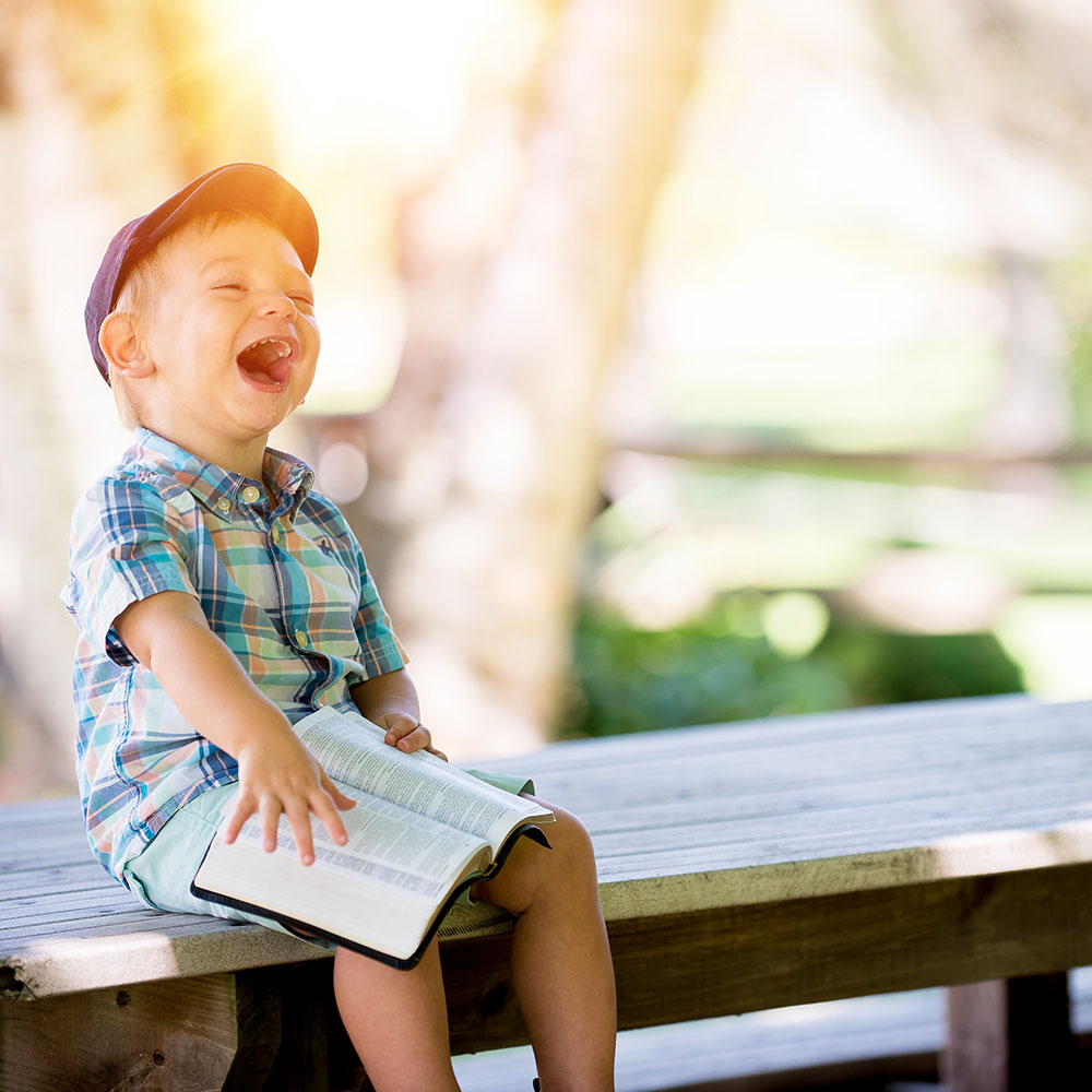 Young boy laughing holding a book